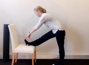 Stretch for tight hamstrings using a chair. Place your foot on the chair for leverage into the stretch.